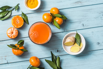 Carrots, ginger, tangerines, turmeric detox fresh juice on blue wooden background, top view. Healthy vegetarian food concept