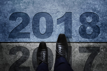 2018 Year Concept, Businessman with Black Oxford Shoes Steps over 2017 into a New Year, Top View, Dark Cement Grunge as background
