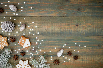 New Year composition with pine cones, gingerbread cookies and fir on wooden background. Flat lay, top view.