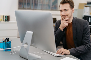 Young man sitting in front of computer at office
