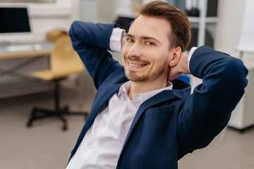Young relaxed man sitting in office