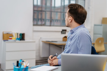 Businessman sitting daydreaming at work