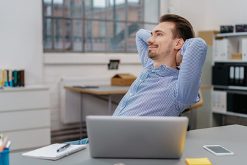 Young happy man relaxing in chair at office