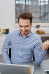 Exultant businessman punching the air with a fist