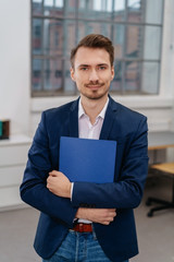 Young man standing with files in office