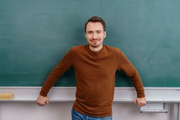 Young smiling man standing against blackboard