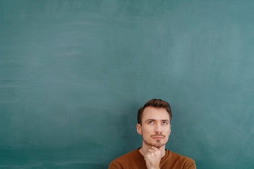 Young pensive man standing against blackboard