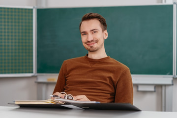 Young smiling man sitting at desk with binder