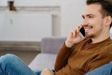 Young smiling man talking on phone at home