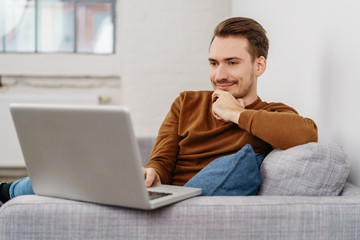 Young man sitting with laptop on sofa