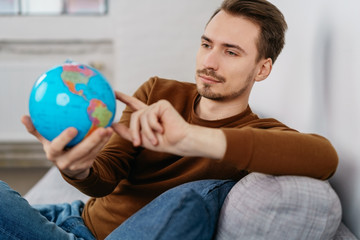 Young man sitting on sofa with globe