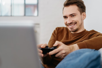 Young smiling man playing TV games