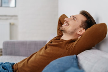 Young smiling man relaxing on sofa at home