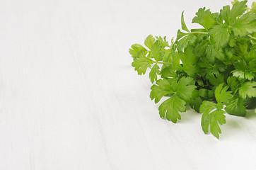 Fresh leaf greens parsley on white wood plank, closeup.