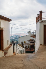 White narrow streets with whitewashed traditional andalusian houses and a view to Mediterranean sea at the horizon at little touristic town village Mijas, Malaga province, Andalusia, Spain.