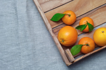 Oranges and tangerines in a wooden box on canvas. Orange juice.