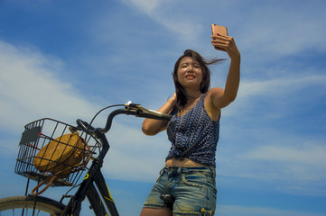 young pretty and happy Asian Chinese girl riding vintage bicycle on the beach taking selfie portrait picture with mobile phone