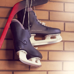 winter sports game/ pair of experienced skates hanging on a hockey stick against a wall