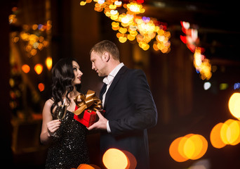 man in suit gives elegant woman a gift box outdoor at night