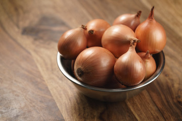 brown onions in steel bowl on old wood table