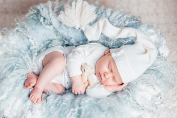 Cute baby in white sleeping with bear toy on a light blue woolen blanket at home. the concept of childhood