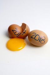 Broken egg with 2017 written and 2018 welcoming years. Happy new years concept.