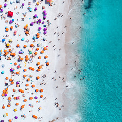 Vertical view of sunny beach and people in the water