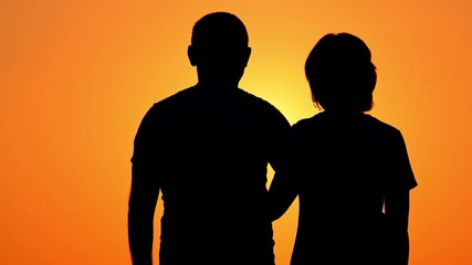 Silhouette of a happy couple. The guy hugs the girl against the sunset in a slow motion. Love of man and woman