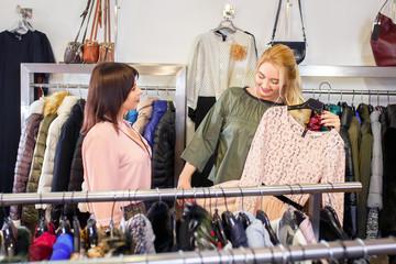 shop assistant helping chooses clothes
