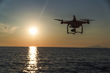 The drone in the sunset sky. ocean wave mountains Close up of quadrocopter outdoors. concept for film maker wedding videography aerial photographer. equipment for vlog blog, old,