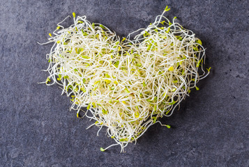 Fresh green alfalfa seed sprouts, superfood and clean eating concept, heart shaped seed sprouts top view.