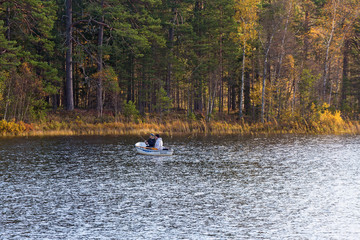 Forest lake with fishermen in a rowboat