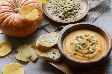 Pumpkin soup in a wooden bowl, with autumn leaves and pumpkin