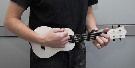 A man plays ukulele