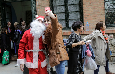 A woman takes a selfie with a man dressed as Santa Claus at a Christmas market in Algiers