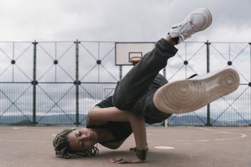 Beautiful woman dancing hip hop in basketball court.