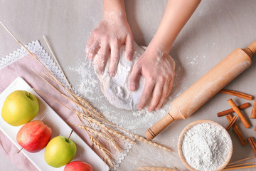 Woman preparing puff pastry on table