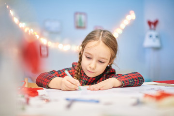 Best gift is gift made by your own hands: cute little girl wearing tartan dress wrapped up in drawing Christmas card for her granny while sitting at desk of modern living room