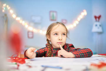 Portrait of adorable little girl looking away pensively while writing letter to Santa Claus, interior of cozy decorated bedroom on background