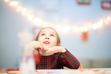 Surprised little girl looking upwards with interest while distracted from drawing Christmas card for her granny, interior of living room decorated for holiday celebration on background