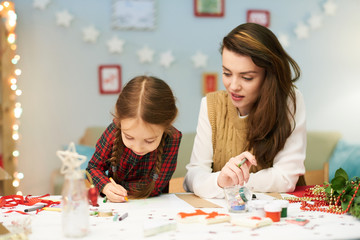 Little girl wrapped up in drawing picture with wax crayons while sitting at desk, her beautiful mother keeping eye on her, interior of living room decorated for Christmas celebration on background