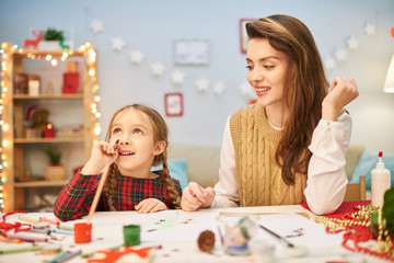 Dreamy little girl distracted from drawing colorful picture and looking upwards with interest, her attractive mother sitting next to her at desk, interior of decorated living room on background