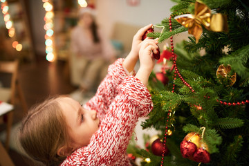 Portrait of dark-haired little girl wearing knitted sweater standing on toes while decorating Christmas tree, blurred background