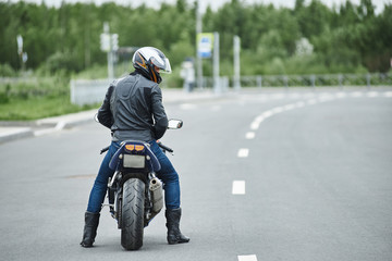 Rear view of unrecognizable Caucasian man motorbiker wearing jeans, leather jacket and boots standing next to his blue parked sport motorcycle and carrying helmet. Extreme Male wait a ride