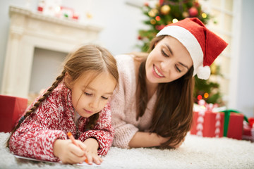 Adorable little girl wrapped up in writing letter to Santa Claus while lying on carpet by fireplace, her attractive mother with charming smile keeping eye on her