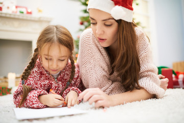 Making Christmas decorations together: cute little girl and her beautiful mother lying on cozy carpet and drawing colorful picture with help of wax crayons, interior of living room on background