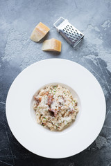 Risotto with chanterelle mushrooms served in a white plate over grey concrete background, vertical shot, view from above