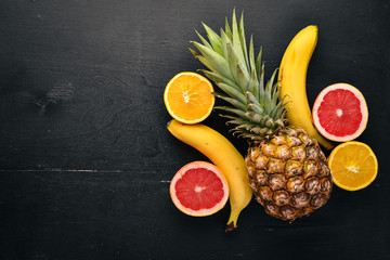 Fresh Tropical Fruits. Coconut, pineapple, kiwi and grapefruit. On a wooden background. Top view. Free space for text.