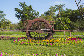 A wooden cart is in the middle of the flower garden.