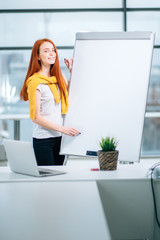 office, business, people and education concept - close up of woman pointing on flip chart
